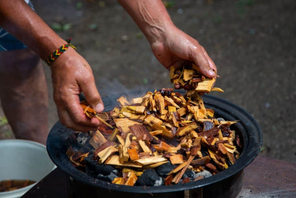 adding soaked wood chips to burning charcoal