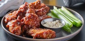boneless chicken wings covered in honey garlic bbq sauce with ranch and celery