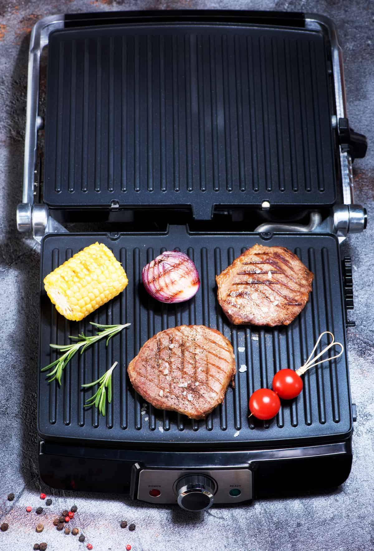 burgers and sausages on a grill pan