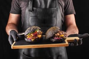 chef holding two big fresh grilled burgers with a black bun ready to eat