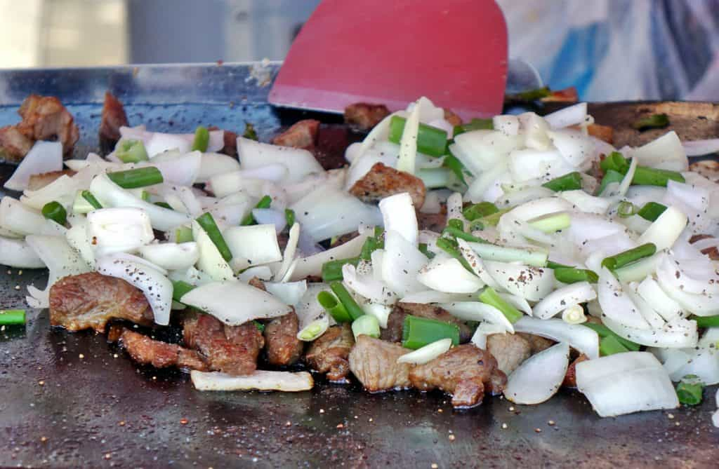 cooking meat and onions on a griddle