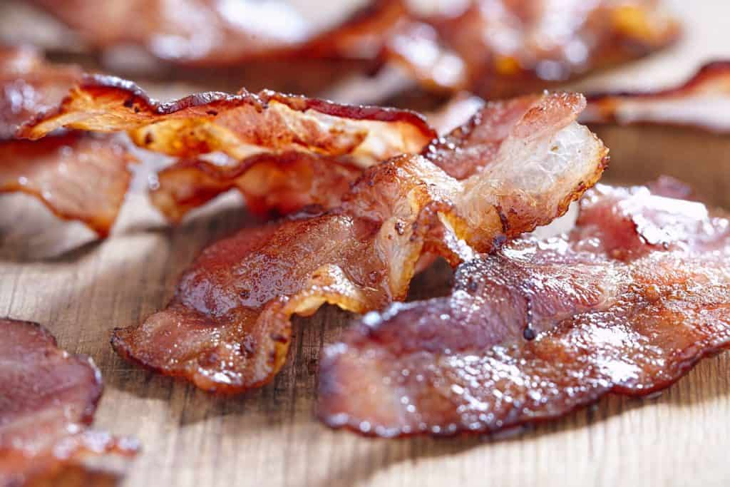 crispy cooked bacon on wooden table