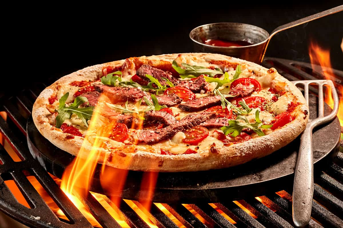 flames reaching up toward pizza on grill