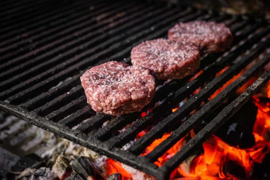grilled hamburgers on charcoal coals