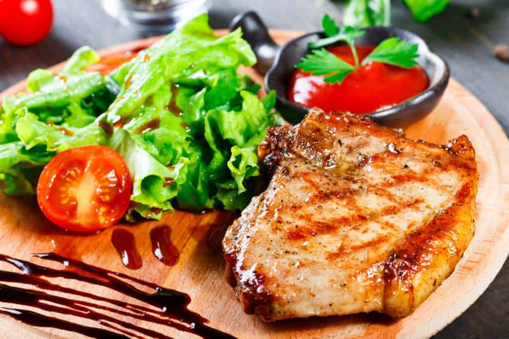 grilled steak pork with fresh vegetable salad tomatoes and sauce on wooden cutting board