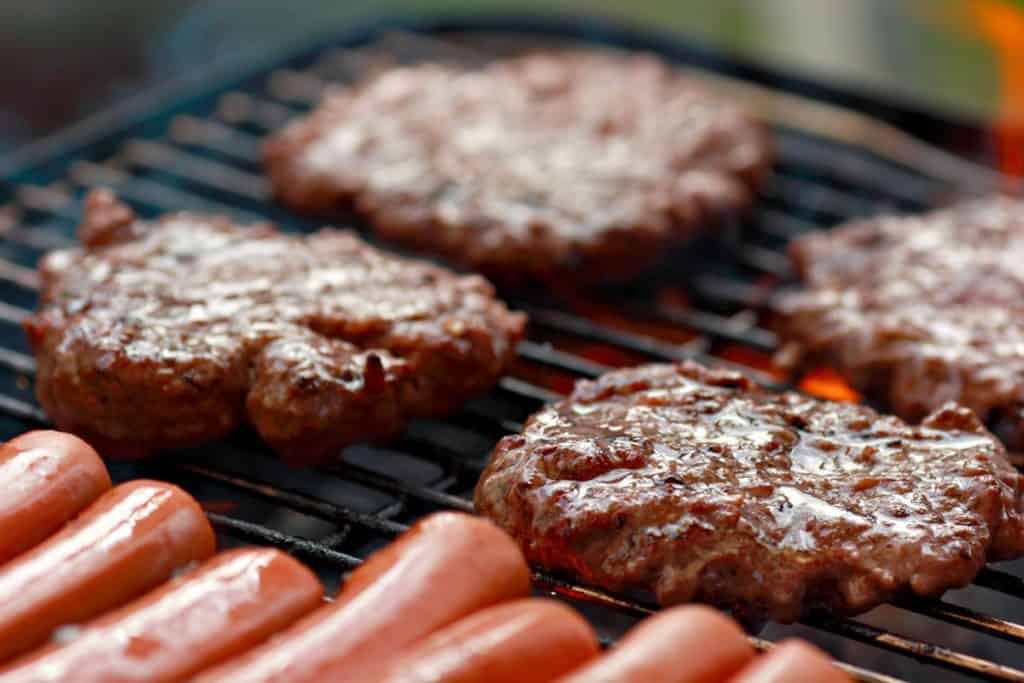 grilling hamburgers and hot dogs at a cook out
