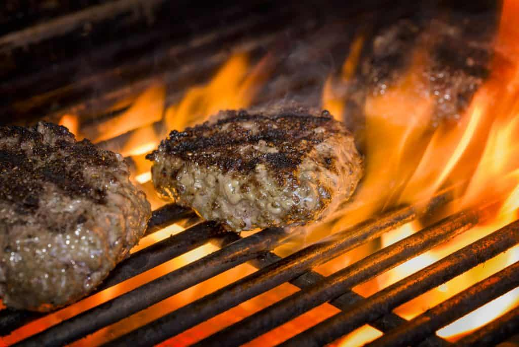 hamburgers on a flaming grill