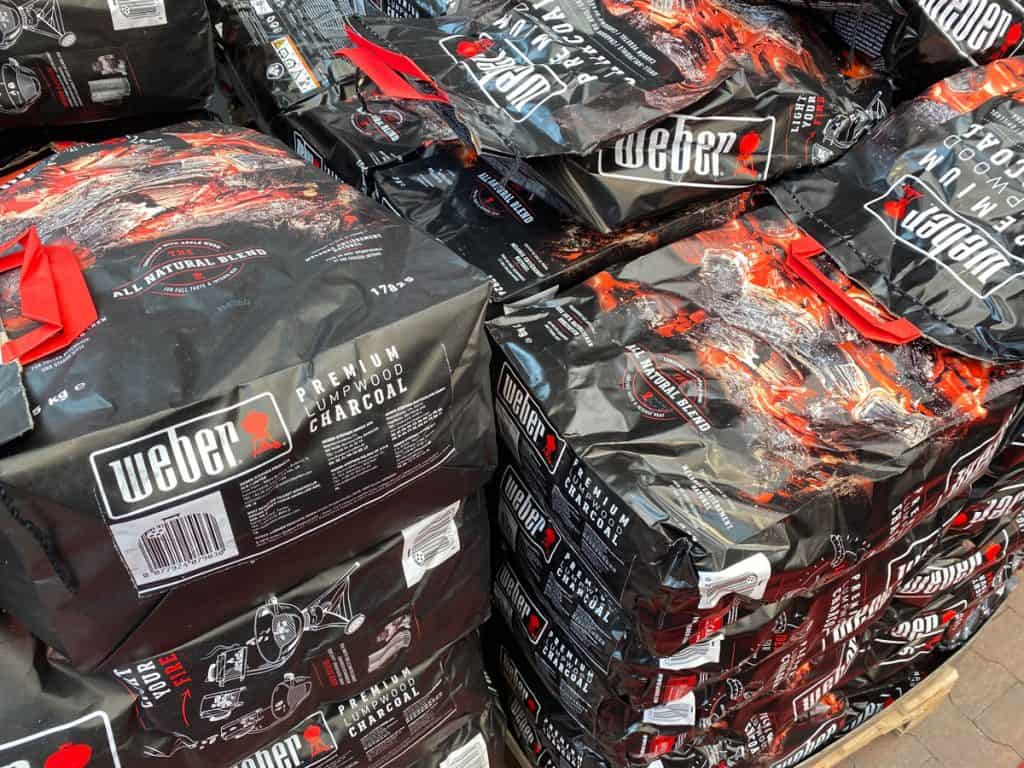 isolated stack of weber grill barbecue charcoal bags in supermarket