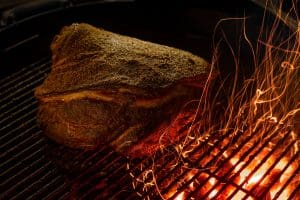 juicy dry rub pork shoulder roast smoked on a charcoal bbq grill