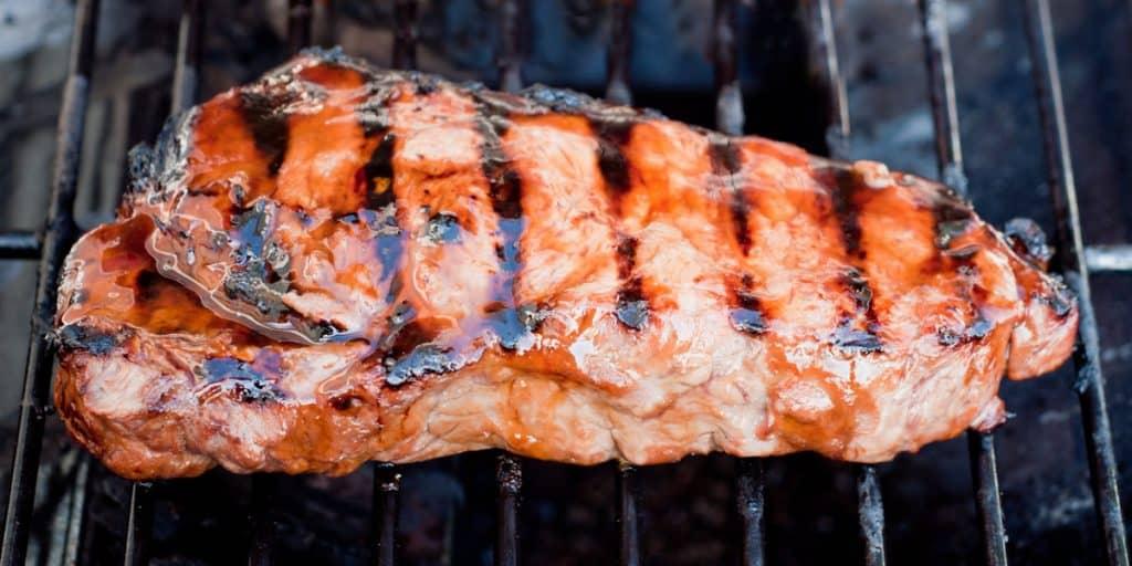juicy new york strip steak on a gas grill