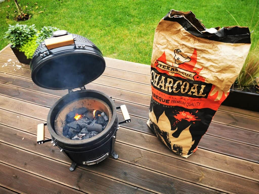 kamado type barbeque grill with a bag of charcoal on a terrace
