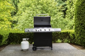 large barbeque cooker with lid up on concrete outdoor patio