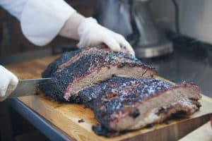 large piece of smoked brisket meat on a wooden board