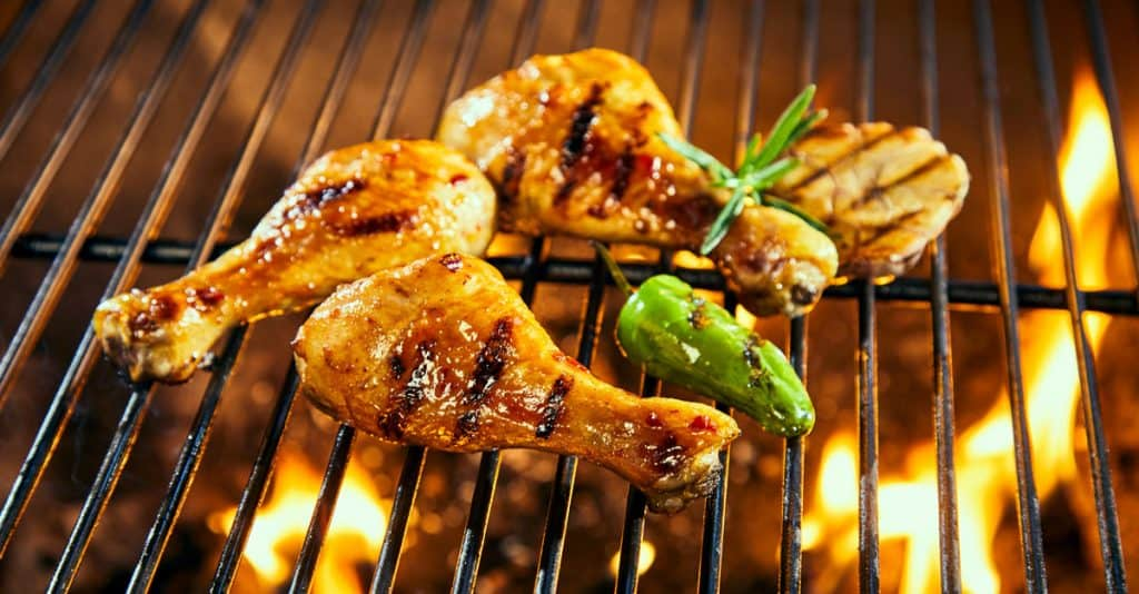 marinated chicken drumsticks grilling on a bbq