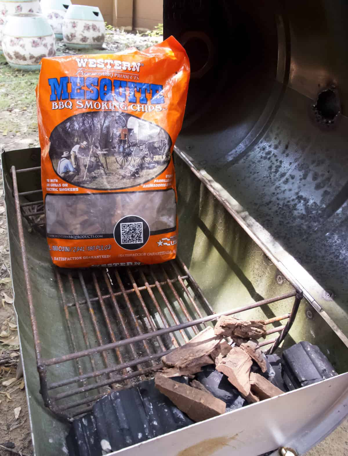 mesquite smoking chips and charcoal in barbecue grill on backyard