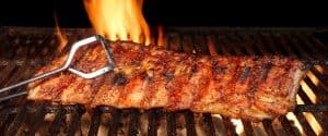 pork ribs roasted on the hot flaming charcoal grill