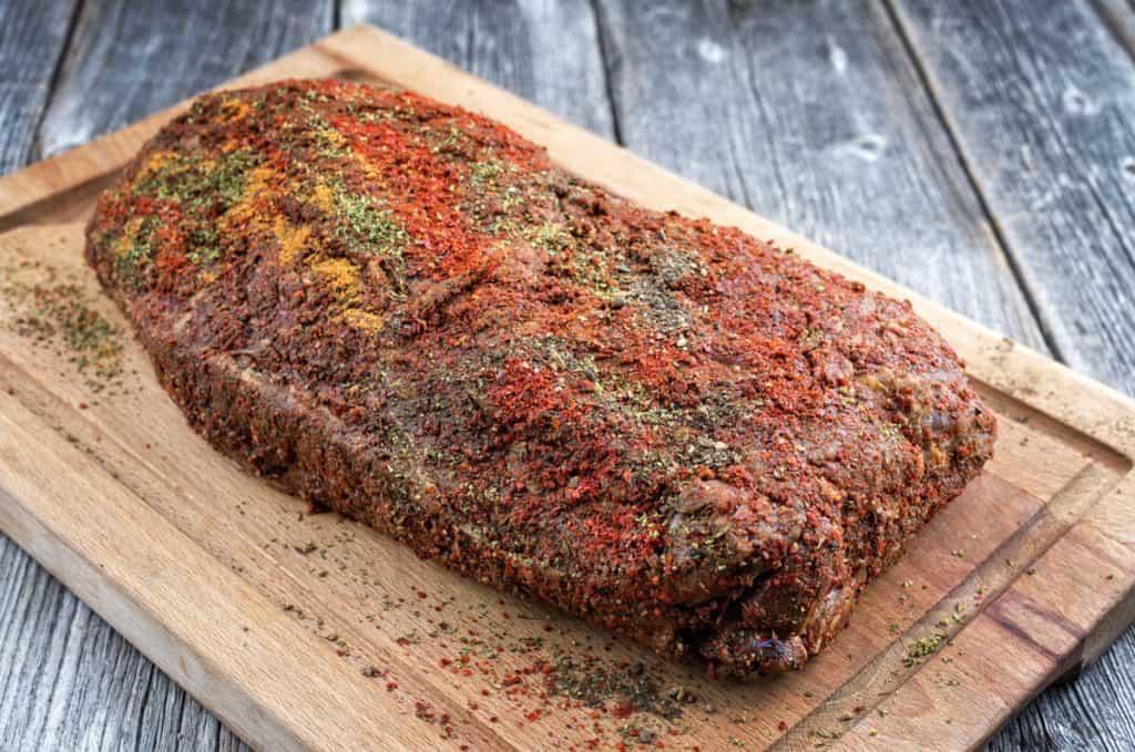 raw boston butt with spicy rub on a wooden cutting board