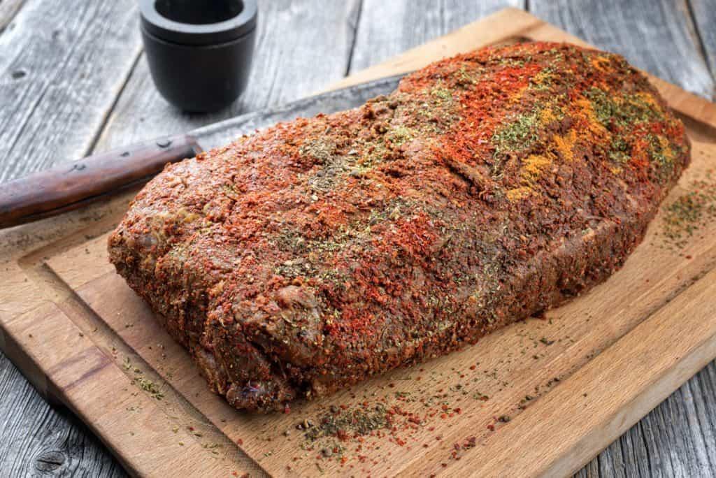 raw pork butt with spicy rub on a wooden cutting board