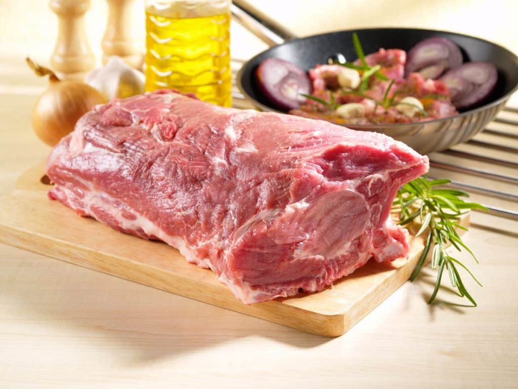 raw pork shoulder square cut on kitchen cutting board