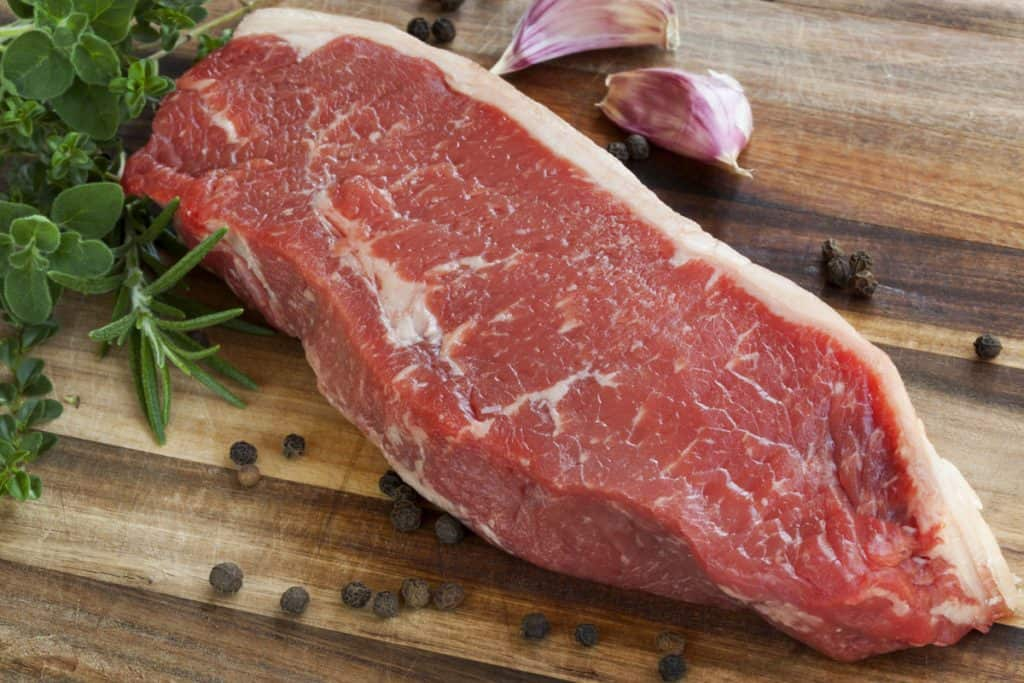 raw sirloin steak with herbs