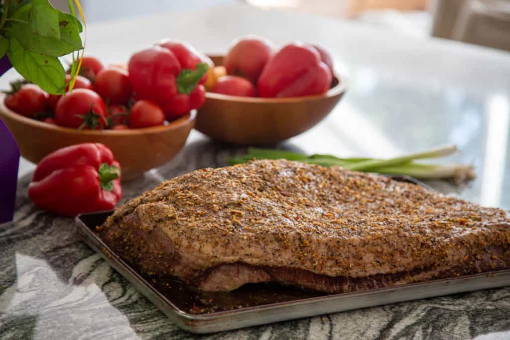 raw spiced rubbed beef brisket on marble kitchen counter