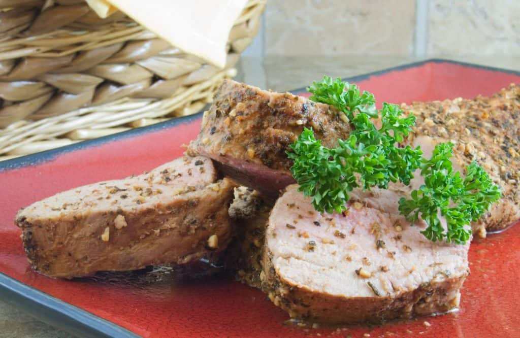 sliced and stacked pork tenderloin garnished with parsley