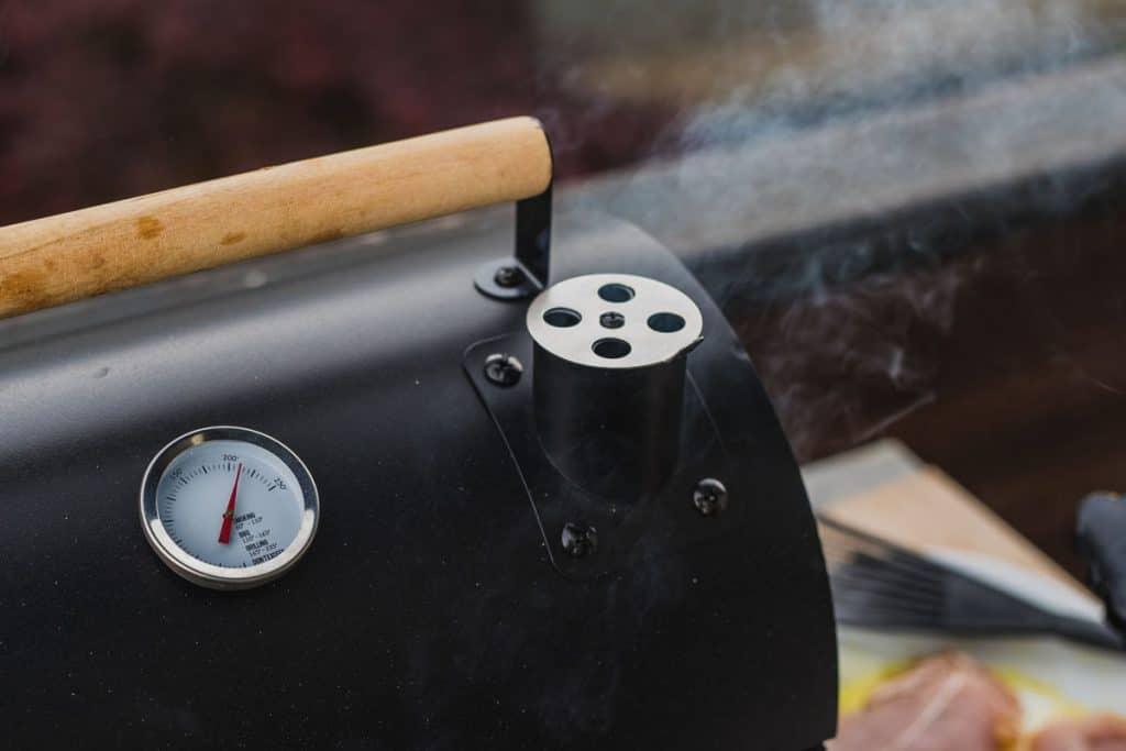 smoke coming out of a smokestack of a small black smoker grill