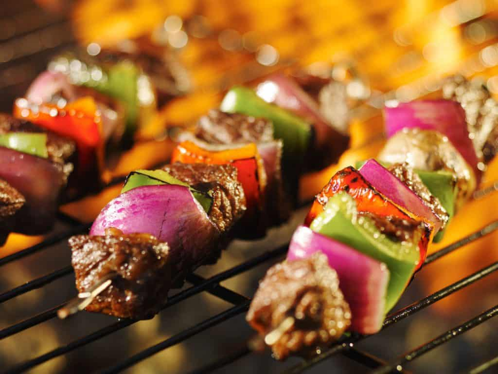 steak shish kabob skewers cooking on flaming grill