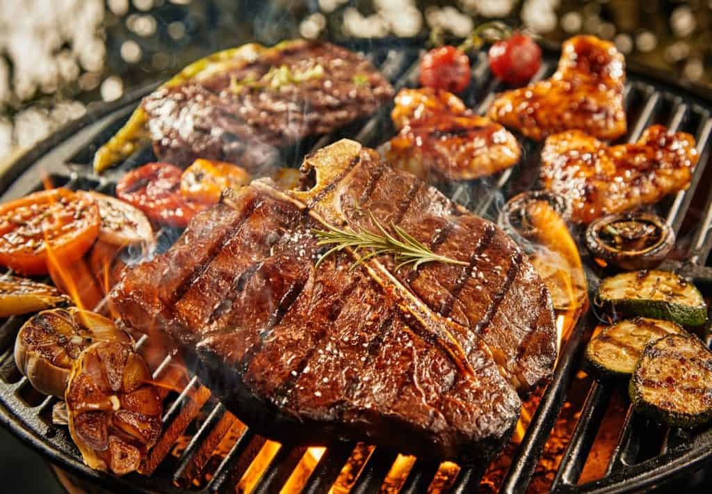 t-bone steak grilling over a portable barbecue