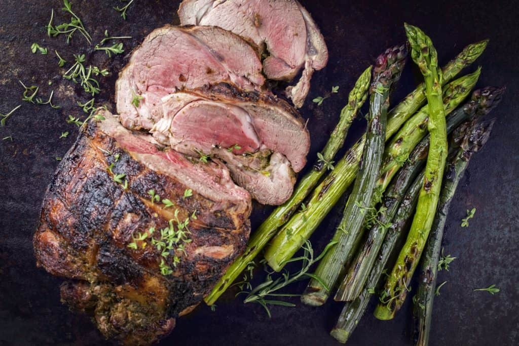 traditional barbecue lamb roast with green asparagus