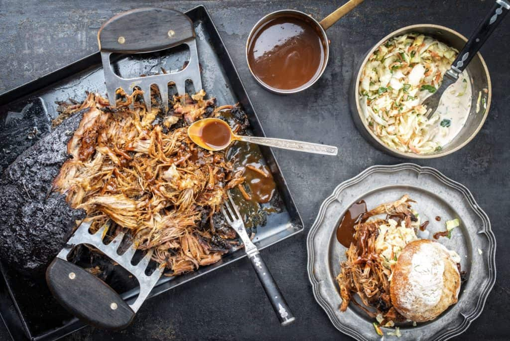 traditional barbecue pulled pork torn to bits with coleslaw and burger on a board