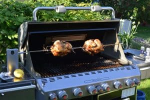 two grilled chicken on a giant weber genesis grill rotisserie